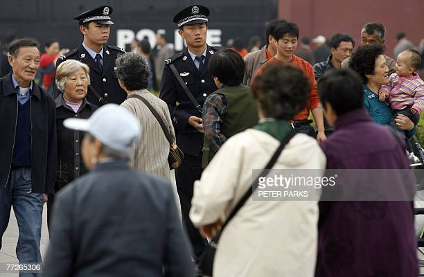 Policemen patrol along Tiananmen Gate in Beijing, 11 October 2007, as China's ruling Communist Party has intensified a crackdown on dissent ahead of...