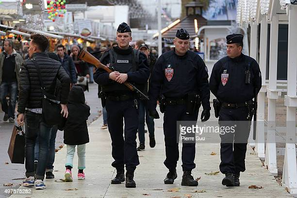 Policemen patrol at the Christmas market on the Champs Elysee on November 19 2015 in Paris France Paris continues to remember those lives lost last...