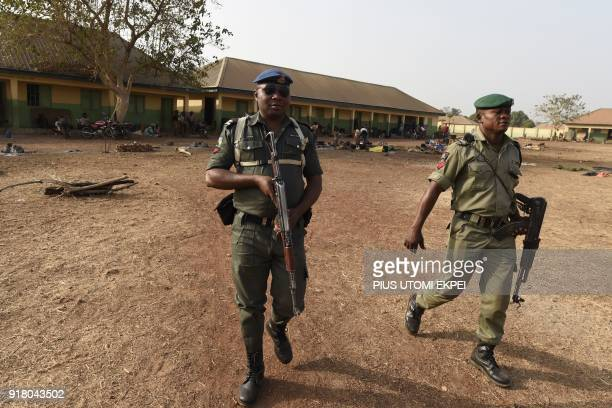 Policemen patrol at the internally displaced people camp occupied largely by women and children affected by herders and farmer's violent clashes from...