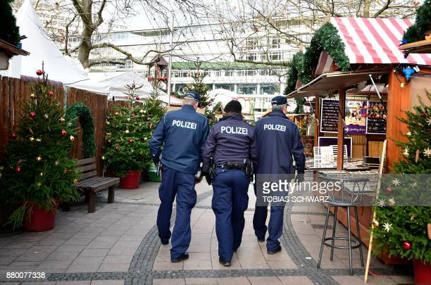 Policemen patrol past stalls of the Christmas market at Berlin's Breitscheidplatz square as the market opens to the public on November 27 2017 The...