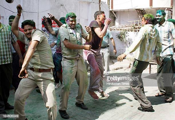 Policemen playing with colors and dancing during Holi celebrations on March 28 2013 in Ghaziabad India Policemen play Holi a day after actual...