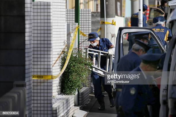 Policemen prepare for inspection in front of an apartment in Zama Kanagawa prefecture on November 2 where police found nine dismembered corpses...