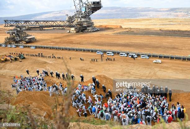TOPSHOT Policemen prevent environmentalist to march further after they managed to enter the Hambach lignite open pit mine near Elsdorf western...