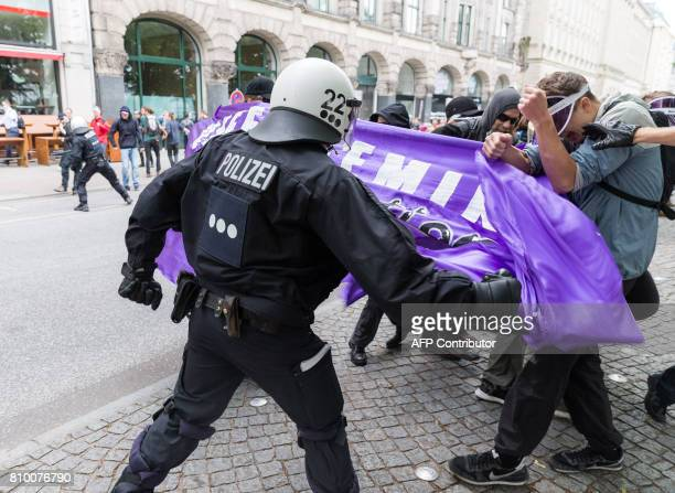Policemen prevent participants of a protest titled 'Color the Red Zone' to enter a cordoned off area on July 7 2017 in Hamburg northern Germany where...