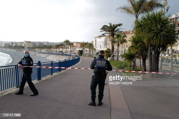 Policemen prohibit access to the beach with warning tapes, on the 'Promenade des Anglais' of the French riviera city of Nice, on February 27, 2021 as...