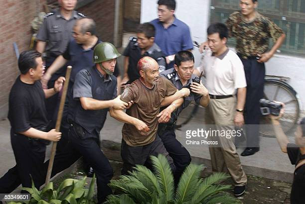 Policemen rescue an elderly hostage out of a house after they subdued a kidnapper at Tangli Village on August 9, 2005 in Zhengzhou of Henan Province,...