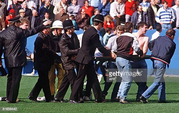 Policemen rescue soccer fans at Hillsborough stadium 15 April 1989 when 96 fans were crushed to death and hundreds injured after support railings...