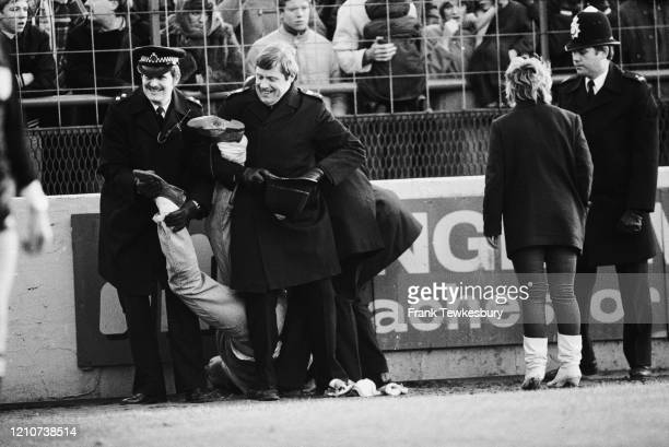 Policemen restraining a fan, holding him by the legs, during the FA Cup Fourth Round match between Leyton Orient and Southampton at Brisbane Road in...