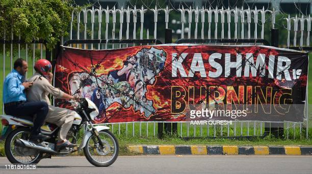 TOPSHOT Policemen ride past a banner hanged near the Parliament building in Islamabad on August 15 as the country observes 'Black Day' on India's...