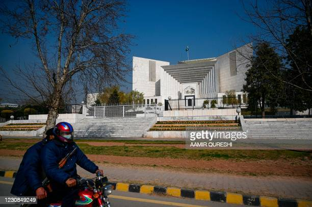 Policemen ride past the Supreme Court building in Islamabad on January 29 where lawyers have filed a last-ditch attempt to overturn the acquittal of...