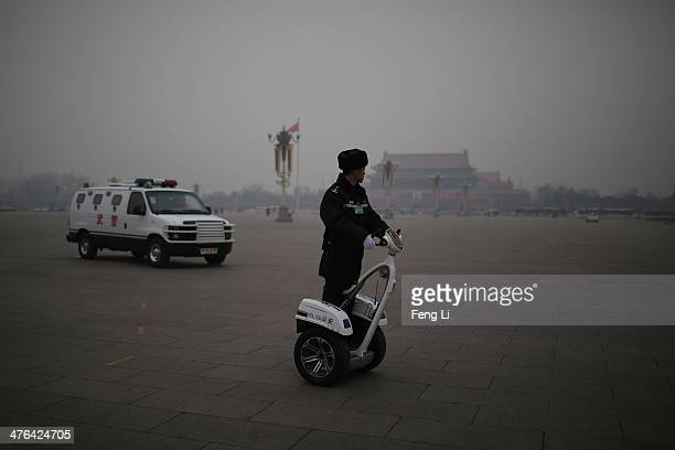 A policemen rides twowheel electronic vehicle patrol on the Tiananmen Square during severe pollution before the opening of the 2nd session of the...