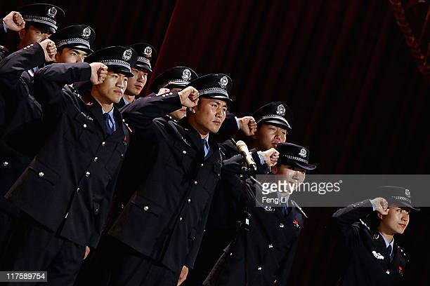 Policemen salute at the admission ceremony of Communist Party of China during a gala show to celebrate the 90th anniversary of the founding of the...