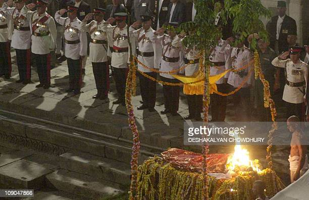 Policemen salute the burning pyre of Nepal's late king Dipendra during his cremation on the banks of the holy river Bagmati in Kathmandu 04 June 2001...