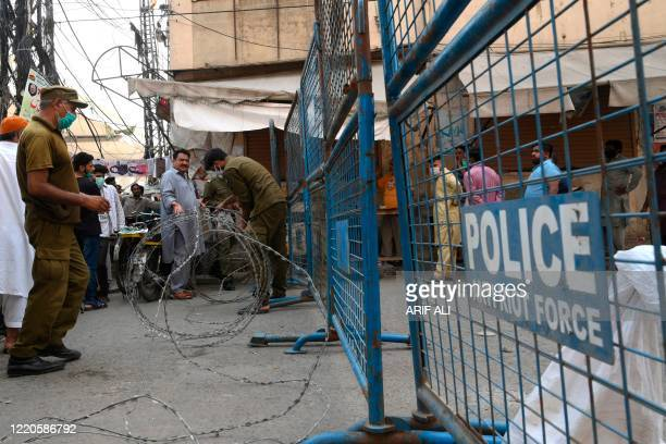 Policemen seal a street at a residential area in Lahore on June 17, 2020 after the COVID-19 coronavirus cases continue to rise. - Pakistan, which has...