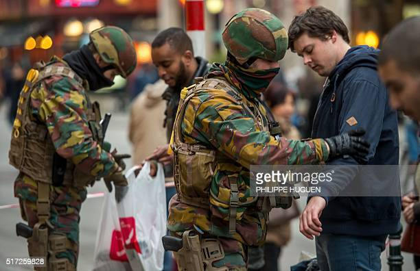 Policemen search passengers at the entrance of the De Brouckere metro station on March 24 2016 in Brussels two days after a triple bomb attack which...