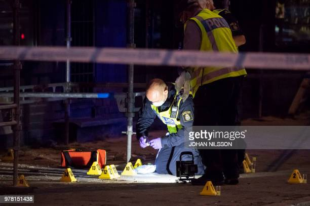 Policemen search the scene after five people were hurt in a shooting in the centre of the southern Swedish city of Malmo on June 18 2018 One person...