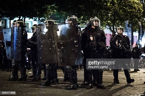 Policemen secure a street as France supporters briefly confront riot police during the celebration on the Champ Elysees after France won the Euro...