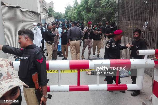 TOPSHOT Policemen secure an area around a body outside the Pakistan Stock Exchange building after a group of gunmen attacked the building in Karachi...