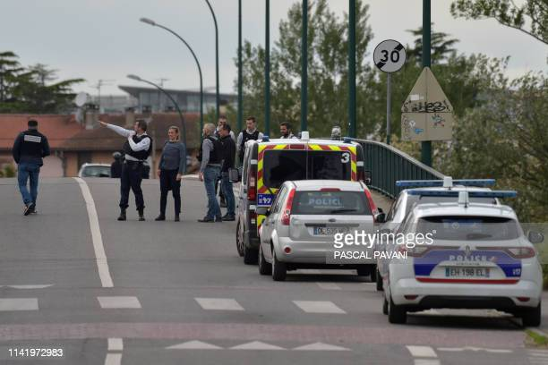 Policemen secure the area around a bar where a man is holding four persons as hostages on May 7 2019 in Blagnac near Toulouse
