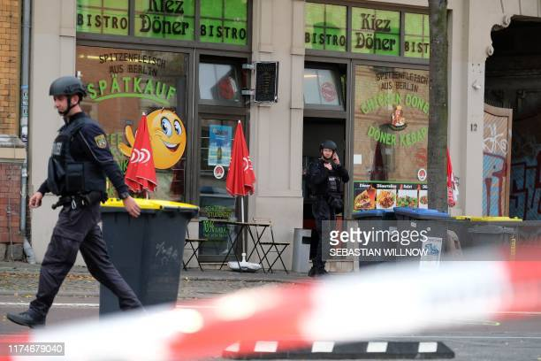 Policemen secure the area around a doner kebab restaurant site of a shooting in Halle an der Saale eastern Germany on October 9 2019 At least two...