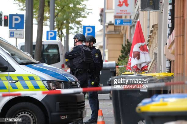Policemen secure the area around the site of a shooting in Halle an der Saale eastern Germany on October 9 2019 At least two people were killed in a...
