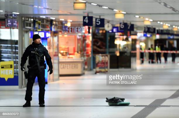 Policemen secure the crime scene after the axe attack on passengers at the main train station on March 9 2017 in Duesseldorf Germany Attackers...