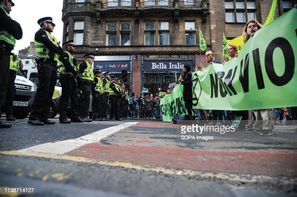 Policemen seen standing guard during the protest Extinction Rebellion held a lockdown of Edinburgh's North Bridge as part of an international...