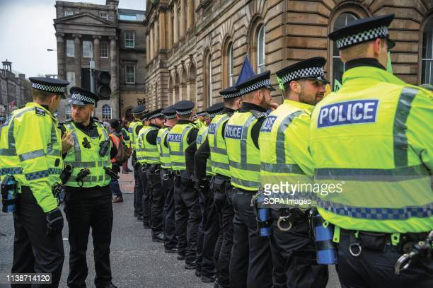 Policemen seen standing on guard during the protest Extinction Rebellion held a lockdown of Edinburgh's North Bridge as part of an international...