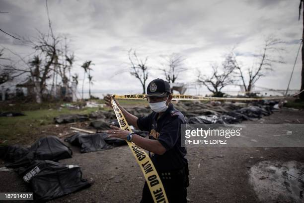 Policemen sets up a cordon where corpses of victims of Super Typhoon Haiyan are lined up in Tacloban, on the eastern island of Leyte on November 14,...