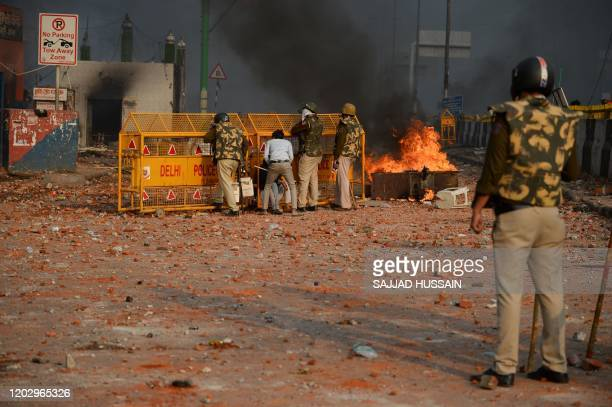 Policemen shelter behind a barrier in a road scattered with stones following clashes between supporters and opponents of a new citizenship law at...