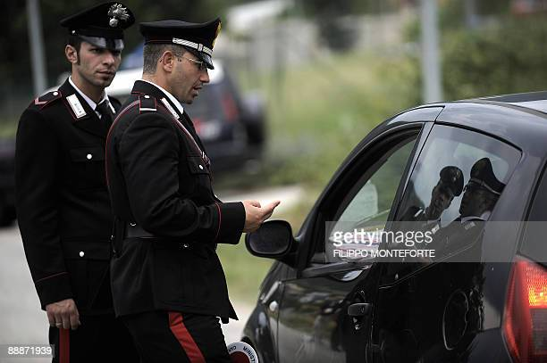 Policemen speak with a car driver at a checkpoint on July 6 2009 near the buildings of the 'Guardia di Finanzia' where a G8 summit will take place...