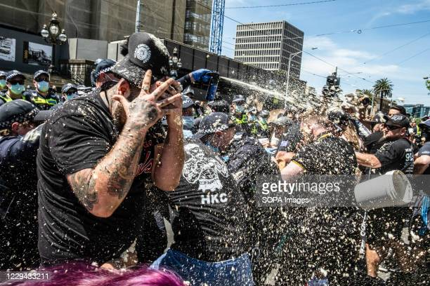 Policemen spray pepper at the protesters during the clashes at Parliament House. Violence erupted at an anti-lockdown protest in Melbourne despite...