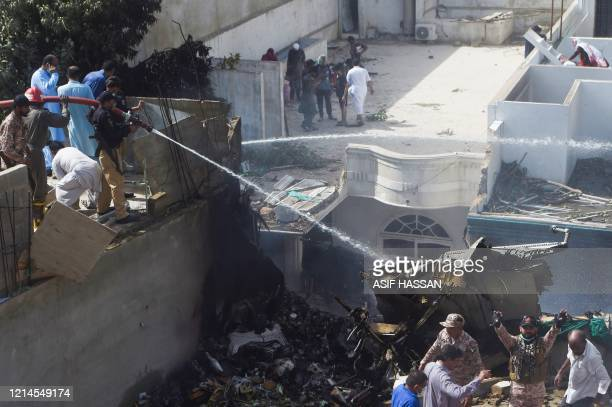 TOPSHOT Policemen spray water on the part of a Pakistan International Airlines aircraft after it crashed at a residential area in Karachi on May 22...