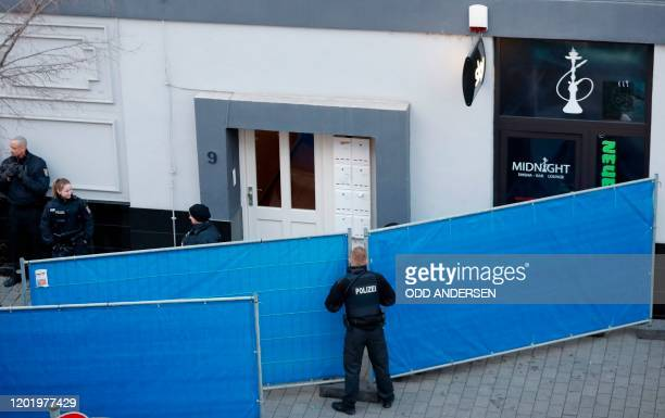 Policemen stand around a sight protection as coroners prepare to carry out a body at one of the crime scenes in Hanau near Frankfurt am Main western...
