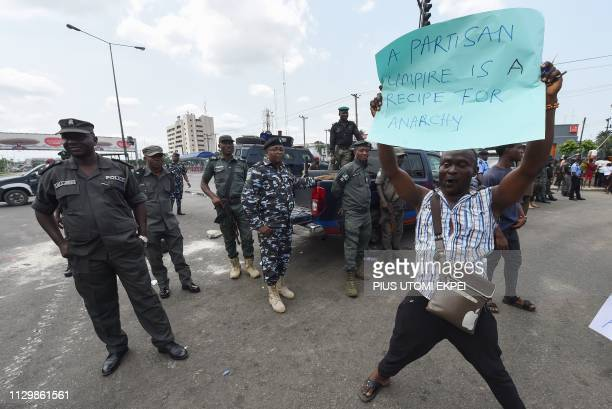 Policemen stand as a man holds a placard to protest against the suspension of governorship elections in Nigeria in Port Harcourt Rivers State on...