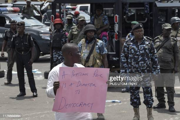 Policemen stand as a protester shouts slogans and waves a placard to protest against the suspension of governorship elections in Port Harcourt Rivers...