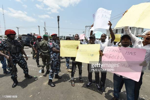 Policemen stand as people shout slogans and carry placards to protest against the suspension of governorship elections in Port Harcourt Rivers State...