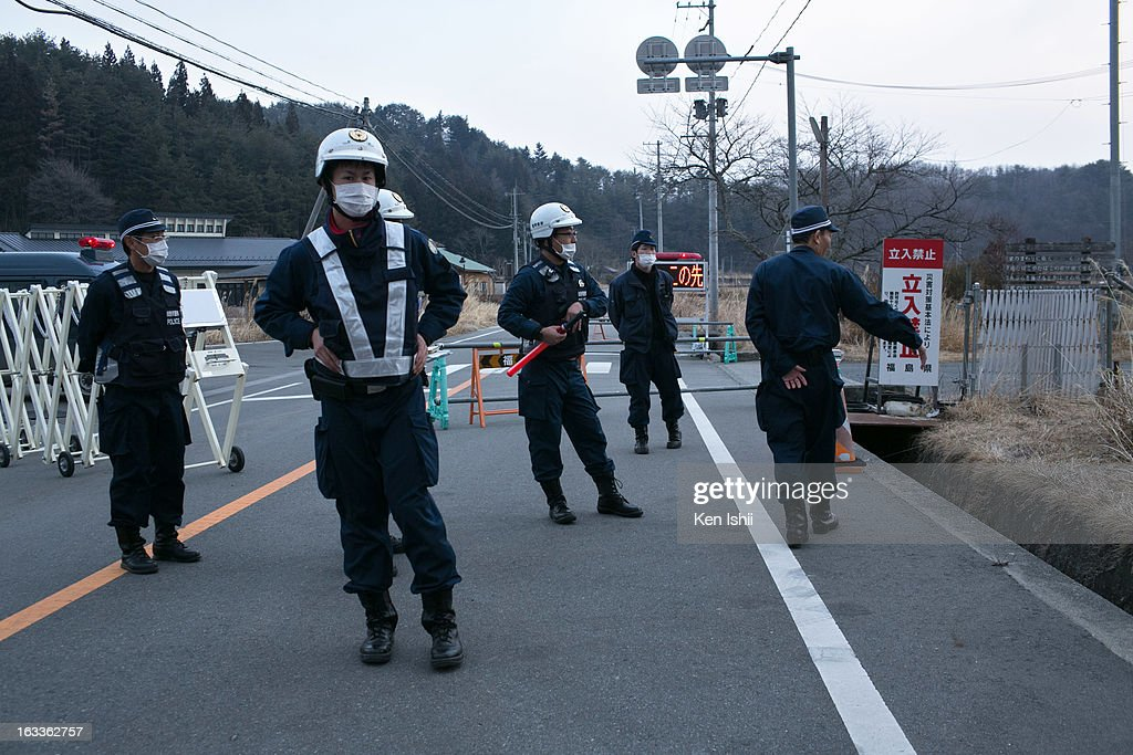 Policemen stand at checkpoint in the village of Tsushima on March 8, 2013 in Namie, Fukushima Prefecture, Japan. Japan is preparing to commemorate the second anniversary of the magnitude 9.0 earthquake and subsequent tsunami that claimed more than 18,000 lives.