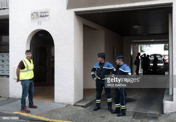 Policemen stand at the entrance of a building after five people including one child were killed when a fire tore through an apartment in Pau...