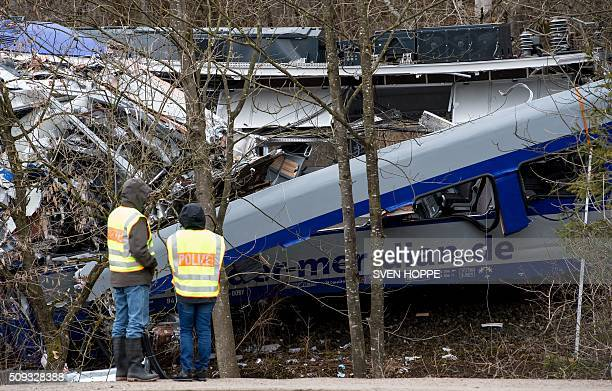 Policemen stand at the site of a train accident near Bad Aibling, southern Germany, on February 10, 2016. Two Meridian commuter trains operated by...