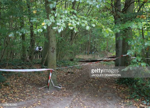 Policemen stand behind a police cordon on September 23 2018 in the Bois de Vincennes in Paris on the site where an explosion in an illegal camp left...
