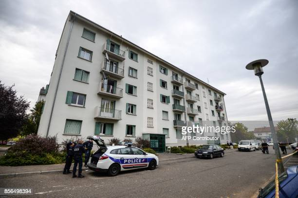 Policemen stand by a building where a fire broke out overnight killing five people in Mulhouse on October 2 2017 / AFP PHOTO / SEBASTIEN BOZON