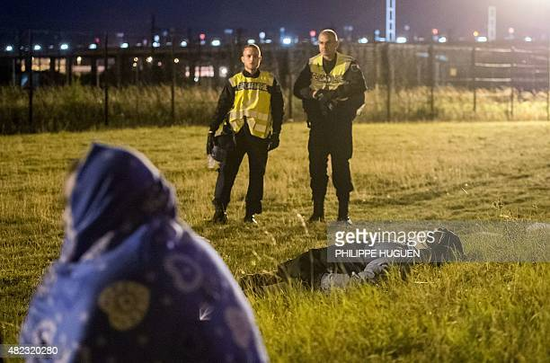 Policemen stand by as migrants rest on the Eurotunnel site in Coquelles near Calais northern France on early July 30 2015 One man died Wednesday in a...