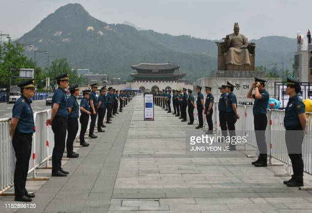 Policemen stand guard along the road before a convoy carrying US President Donald Trump travels to the South Korean presidential Blue House in Seoul...