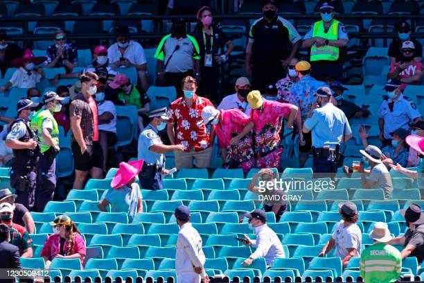 Policemen stand guard among sections of the crowd as the game was halted after allegedly some remarks were made by the spectators on the fourth day...