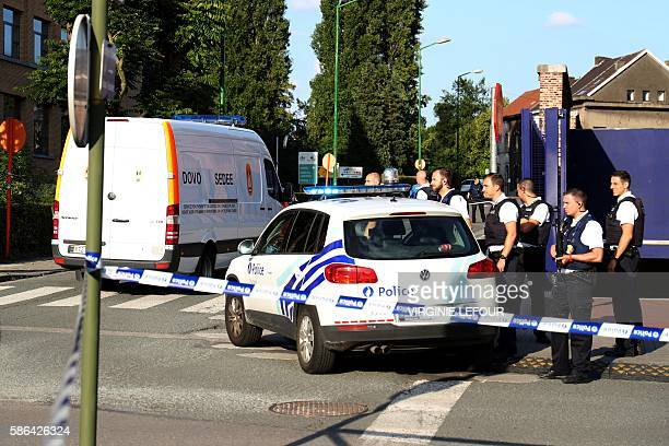 Policemen stand guard as a Belgian Army Mine Clearance Department van arrives inside the security perimeter around the police building in the...