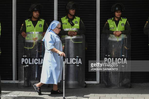 TOPSHOT Policemen stand guard as a nun walks by during a demonstration by university students against the crisis in the public education budget cuts...