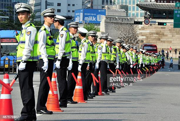 Policemen stand guard as South Korean workers march during a May Day rally in Seoul on May 1 2014 The rally drew around 5000 people who denounced...