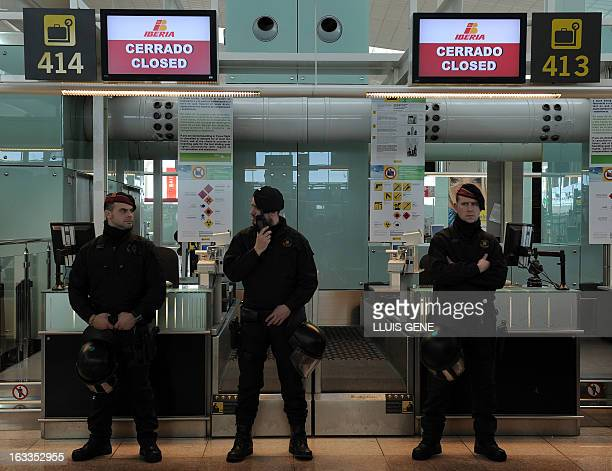 Policemen stand guard as strikers of Spanish airline Iberia demonstrate at Barcelona's El Prat airport in El Prat de Llobregat on March 6 2013...