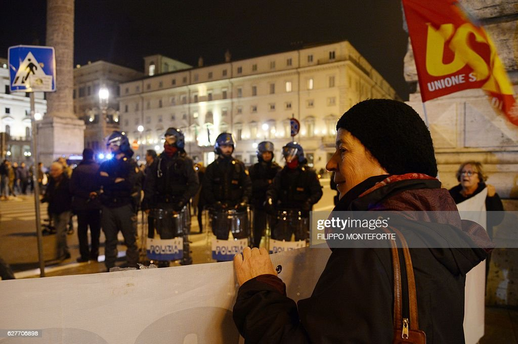 Policemen stand guard as supporters of the 'NO' at the constitutional referendum celebrate near the Palazzo Chigi, on December 4, 2016 after the end of the vote in Rome. Italian voters on Sunday overwhelmingly rejected constitutional reform proposals on which Prime Minister Matteo Renzi has staked his political future, exit polls suggested. / AFP / Filippo MONTEFORTE